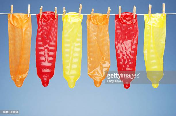 colorful condoms hanging on clothesline - rubber stock pictures, royalty-free photos & images