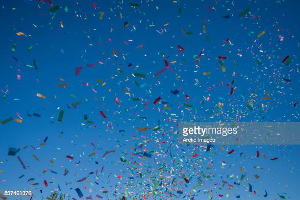 colorful confetti against a blue sky - celebration stock pictures, royalty-free photos & images