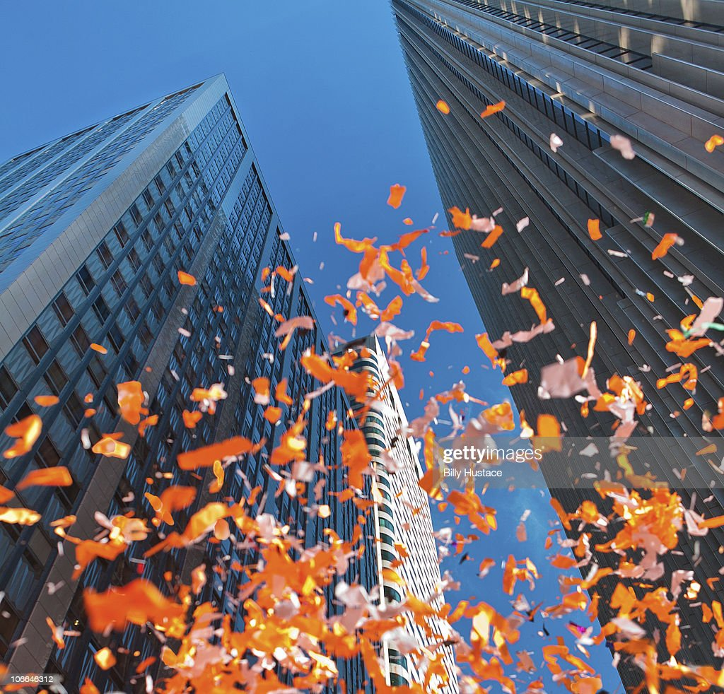 Colorful confetti in sky near office buildings. : Stock Photo
