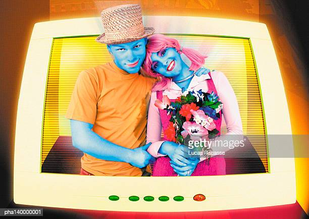 Colorful couple hugging, emerging from computer monitor, woman holding flowers, digital composite.