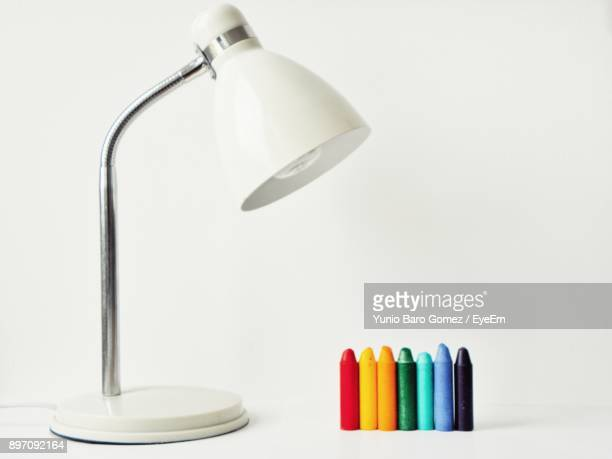 Colorful Crayons By Lamp Over White Background