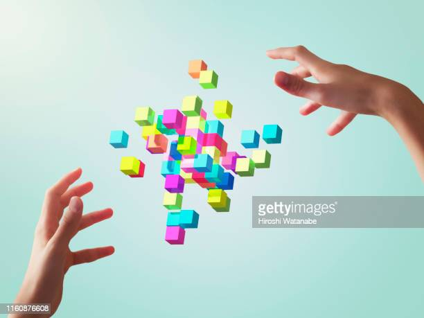 colorful cubes forming geometric shapes with girls hands - kontrolle stock-fotos und bilder
