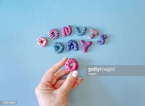 colorful donuts day letters text on blue background made with plasticine. woman hand holding letter. national donut day - 粘土 ストックフォトと画像