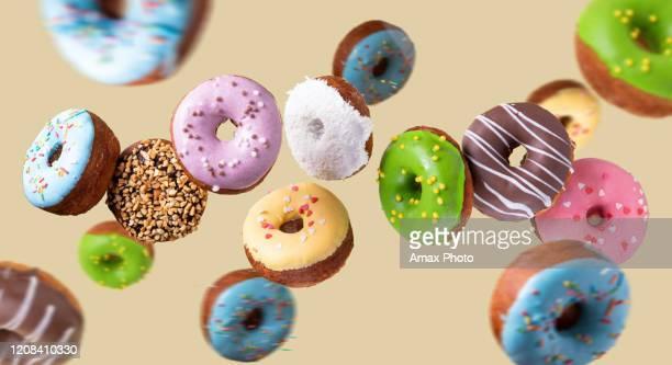 カラフルなドーナツは黄色の背景に飛んで。甘い食べ物の背景。 - ペストリー生地 ストックフォトと画像