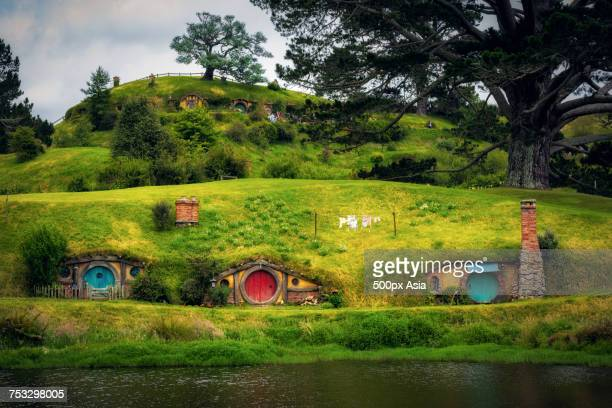 colorful dugouts and pond at hobbit village, new zealand - image foto e immagini stock