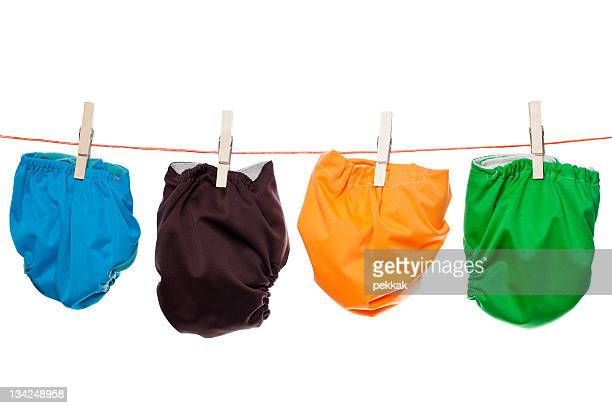 Colorful durable baby diapers hanging on clothesline with white background