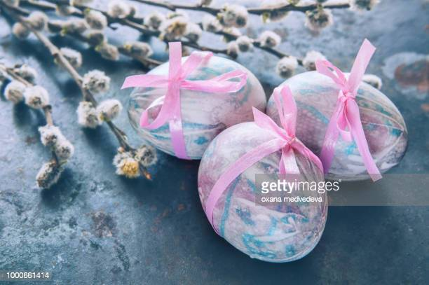 Colorful Easter eggs lying on a beautiful vintage background with bouquet made of willow...