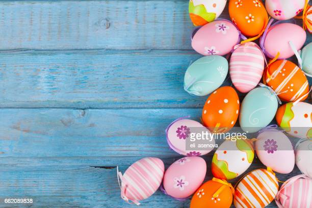 colorful easter eggs on turquoise wooden table - pasqua foto e immagini stock