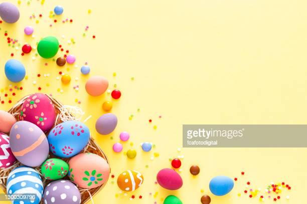 uova di pasqua colorate con caramelle e spruzzi di zucchero su sfondo giallo. spazio di copia - cesto pasquale foto e immagini stock