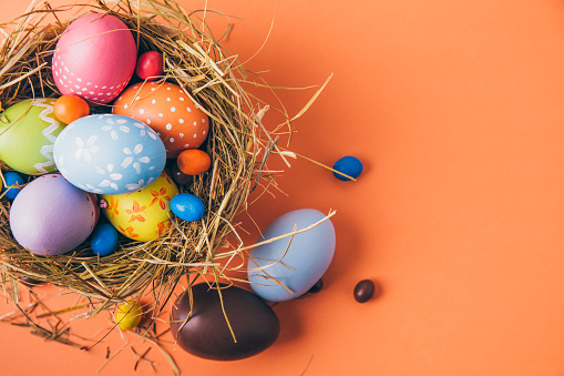 Colorful easter eggs with chocolate and candies in a nest on a orange background 1129603050