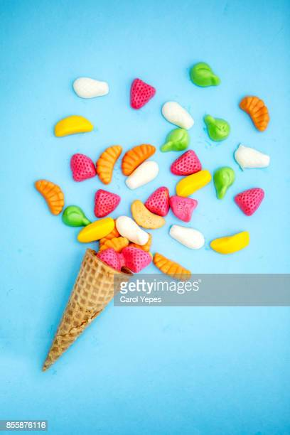 colorful explosion of candies in ice cream cornet on blue background. - funky stock pictures, royalty-free photos & images