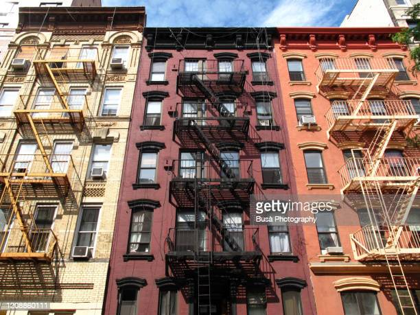 colorful facades of traditional tenement buildings with fire escapes in the east village, manhattan, new york city, usa - east village stock pictures, royalty-free photos & images