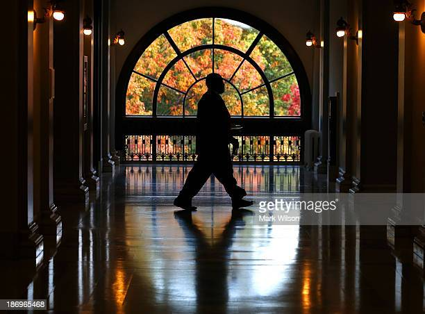 Colorful fall foliage is visible through a window as a Capitol Hill staffer walks the hall in the Russell Senate Office Building November 5, 2013 in...