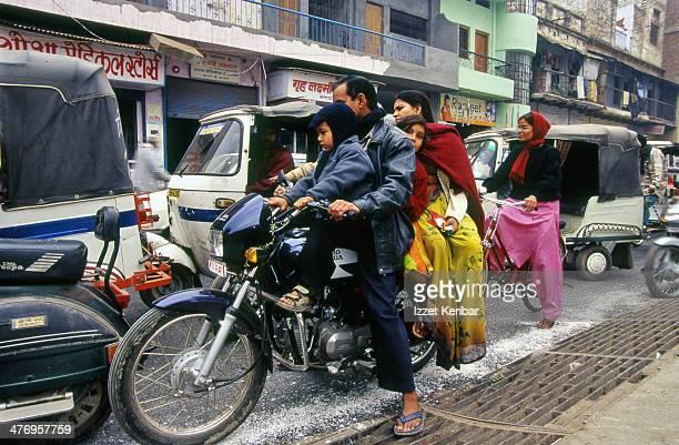 Colorful family of 4 on a motorcycle at Varanasi