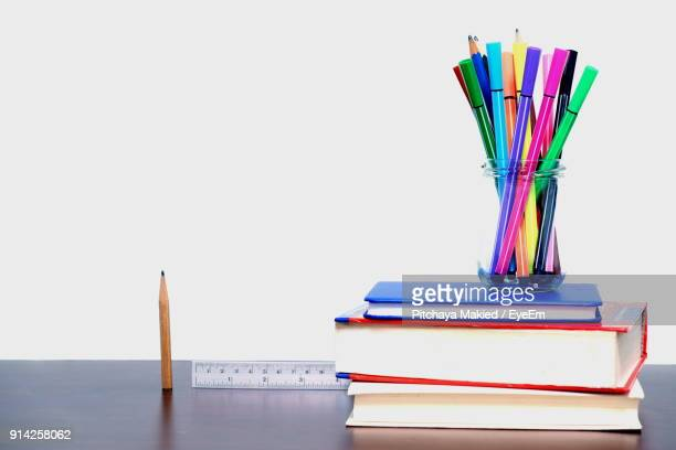 Colorful Felt Tip Pens With Books On Table Against White Background