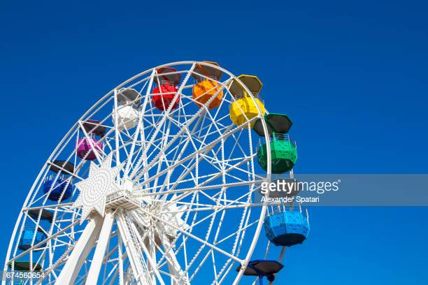 Colorful ferris wheel agains clear blue sky