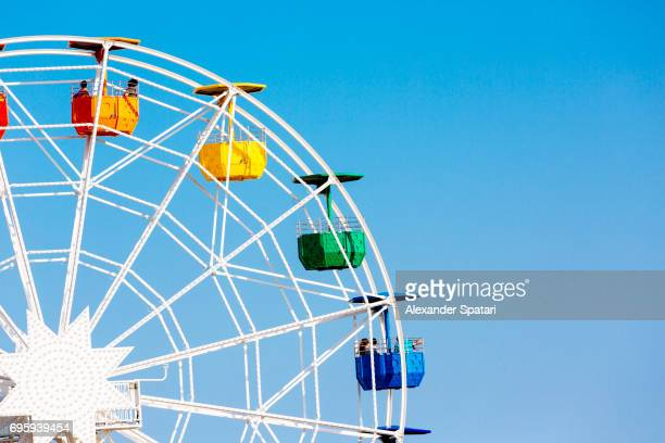 colorful ferris wheel against clear blue sky - 観覧車 ストックフォトと画像