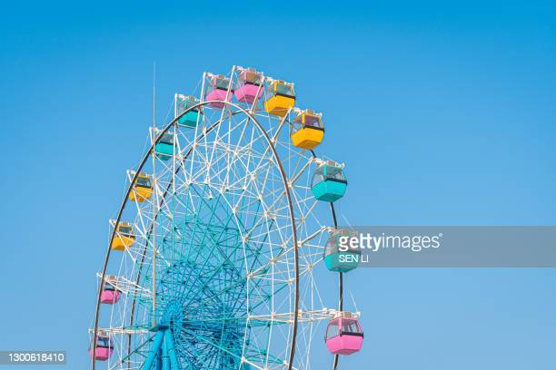 colorful ferris wheel in an amusement park against blue sky - traditional festival stock pictures, royalty-free photos & images
