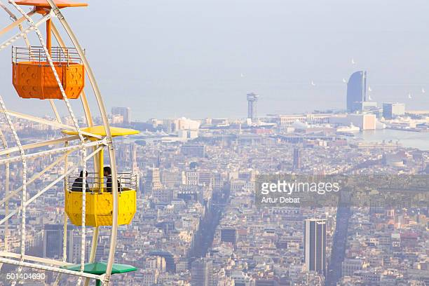 Colorful ferris wheel in the Tibidabo amusement park mountain with the Barcelona city view.