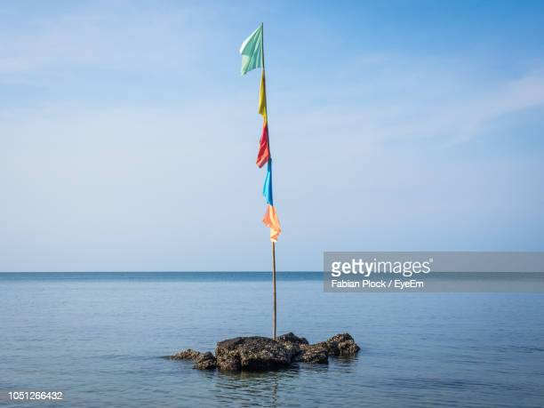 colorful flag pole on rock in sea against sky - flagpole stock pictures, royalty-free photos & images