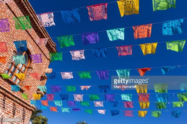 colorful flags, todos santos, mexico - todos santos mexico fotografías e imágenes de stock