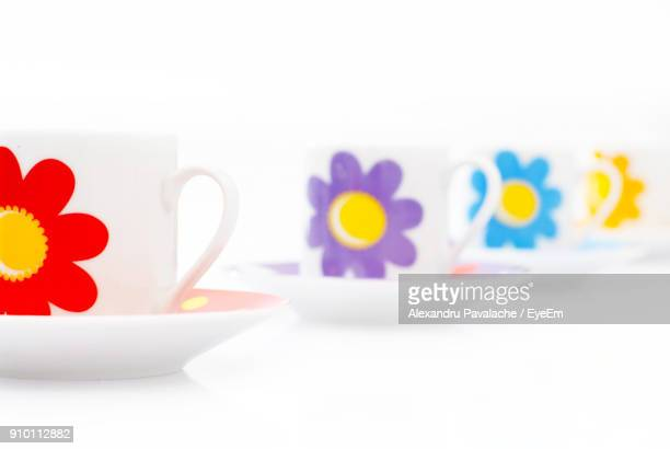 Colorful Floral Patterns On Cups Arranged Over White Background