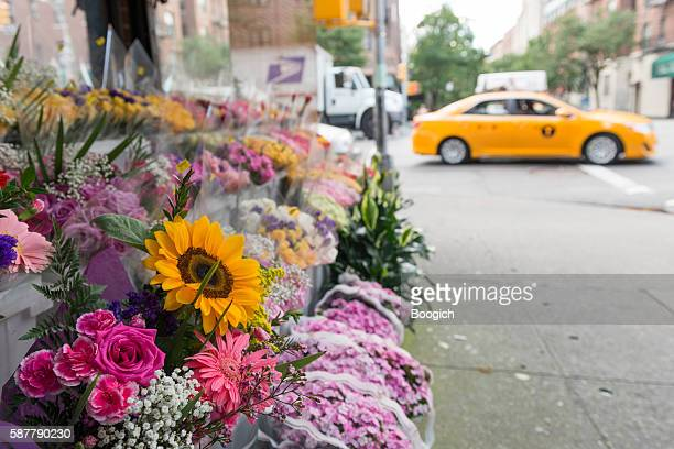 colorful flowers for sale on nyc sidewalk street scene - chelsea new york stock photos and pictures