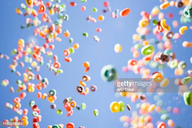 colorful fruit loops cereals levitating in the sky in a beautiful visual effect. - cereal plant stock pictures, royalty-free photos & images