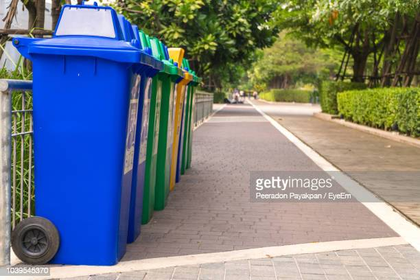 Colorful Garbage Cans Arranged In Row On Footpath At Park