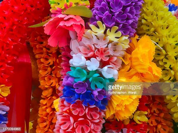 colorful garland at thai temple for worship buddha image. - garland stock pictures, royalty-free photos & images