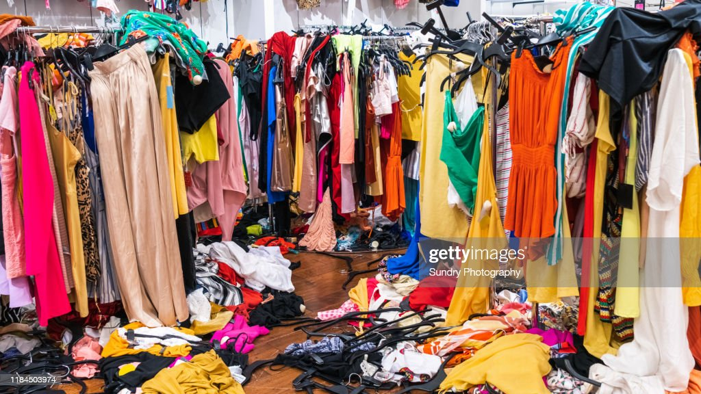 Colorful garments on racks and on the floor; fast fashion concept : Stock Photo