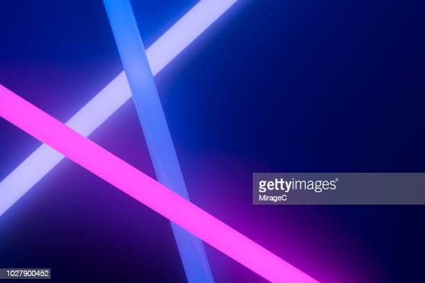 colorful glow sticks crossing - verlicht stockfoto's en -beelden