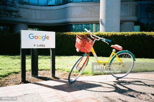 A colorful Google Bike is parked near a sign with logo for Google Inc at the Googleplex the Silicon Valley headquarters of search engine and...