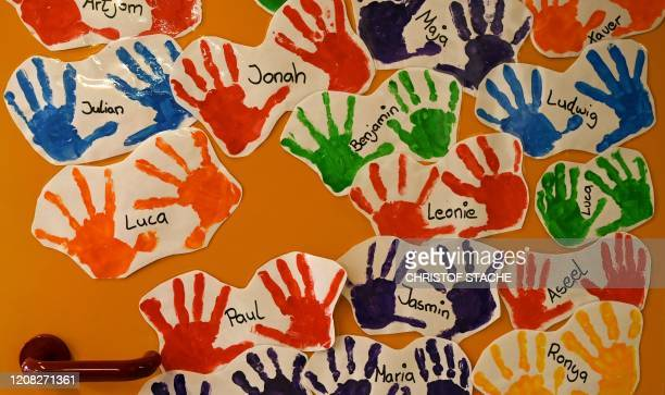 Colorful handprints of children decorate the door of a closed kindergarten in Eichenau, southern Germany, on March 26 as public life in Bavaria has...