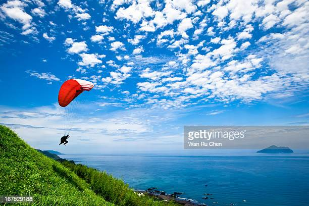 colorful hang glider in sky over blue sea