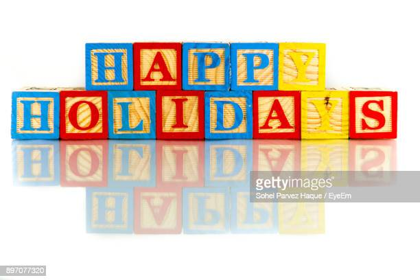 colorful happy holidays toy blocks text against white background - happy holidays stock photos and pictures