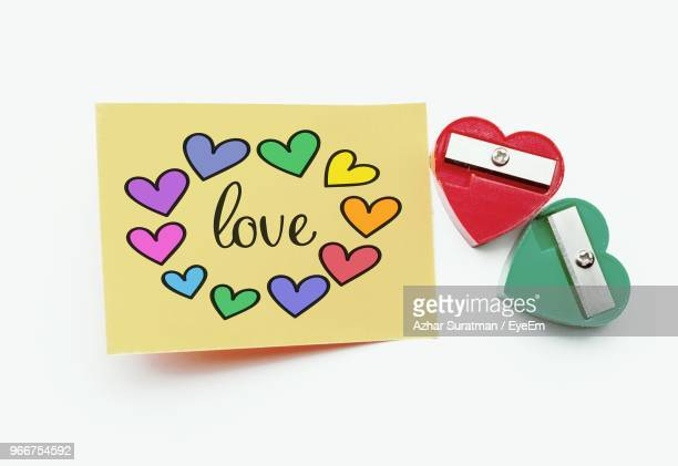 Colorful Heart Shapes With Love Text By Pencil Sharpeners On Adhesive Note Over White Background