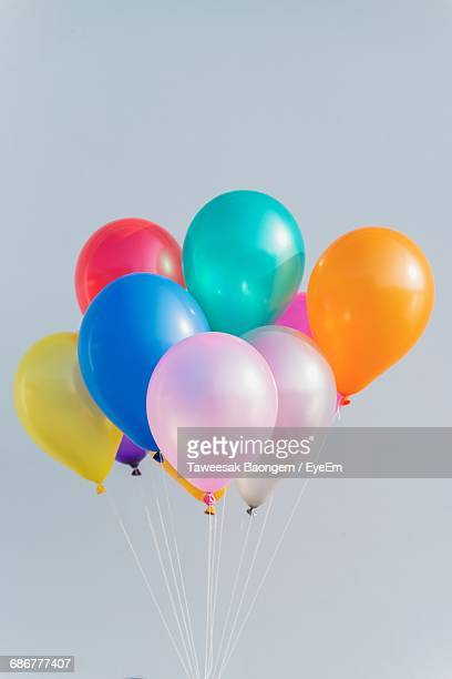 Colorful Helium Balloons Against Clear Sky
