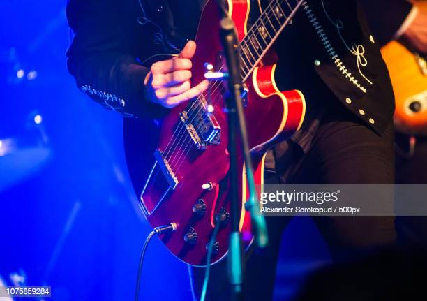 colorful highlighted guitar on rock concert - modern rock stock pictures, royalty-free photos & images