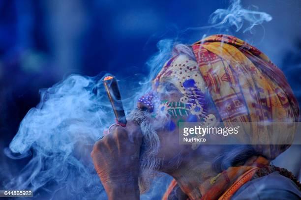 A colorful Hindu Sadhu or Holy Man smokes marijuana at the premises of Pashupatinath Temple during the celebration of Maha Shivaratri Festival at...