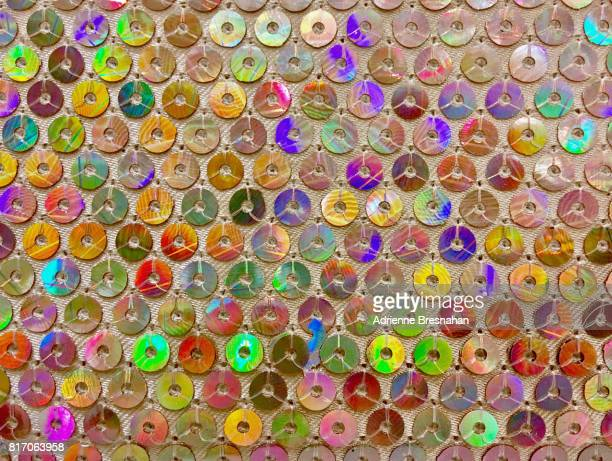 Colorful, Holographic Sequins Stitched on Pink Fabric