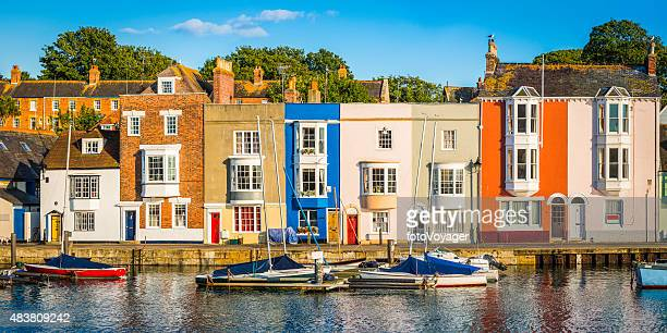 colorful homes quaint cottages in sunny fishing village harbor panorama - fishing village stock pictures, royalty-free photos & images