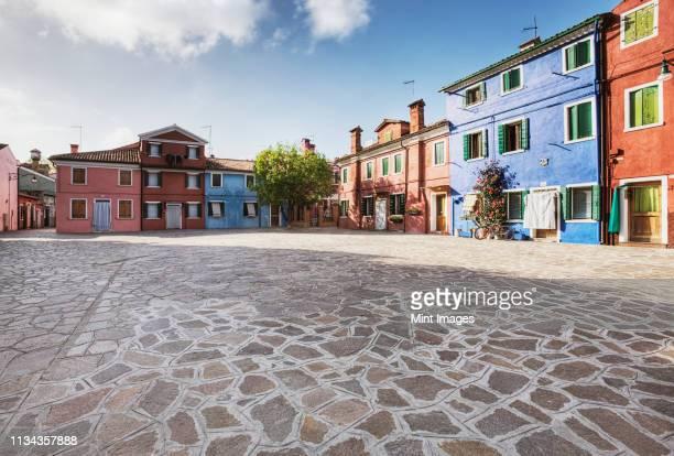colorful homes surround a flagstone plaza - 敷石 ストックフォトと画像