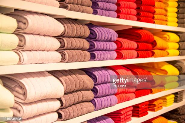 colorful horizontal various fluffy bathing towels on wooden shelf - artículos domésticos fotografías e imágenes de stock