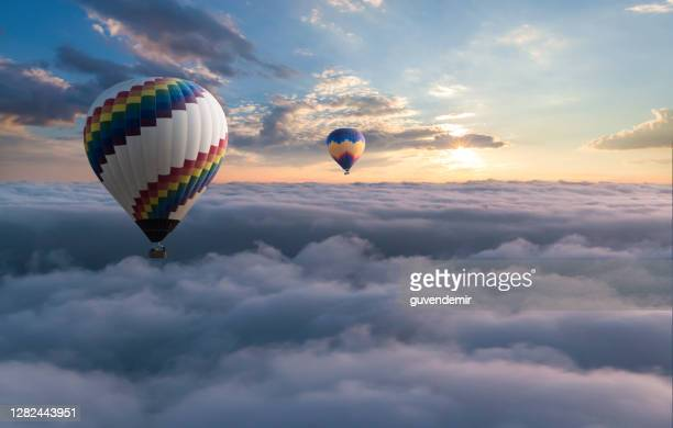 colorful hot air balloon flying above the clouds - moving up stock pictures, royalty-free photos & images