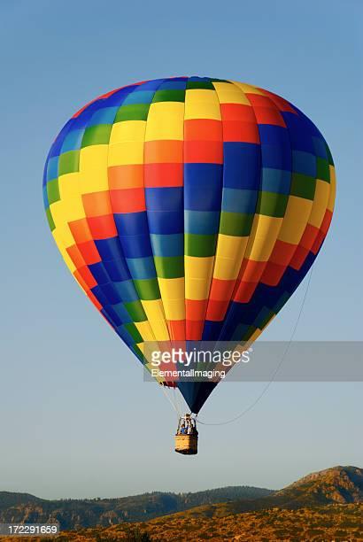鮮やかな山の上を飛ぶ熱気球