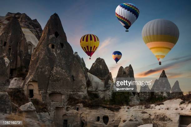 colorful hot air balloons flying over cappadocia in the morning - rock formation stock pictures, royalty-free photos & images