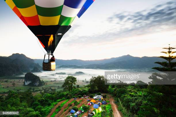 Colorful hot air balloons flying over mountain national park with sunrise and morning mist at Phayao provinceThailand.