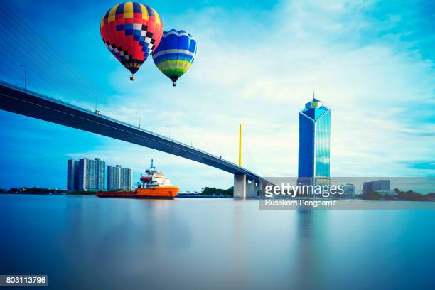 Colorful hot air balloons flying over Rama 9 bridge Chaopraya river at sunset time