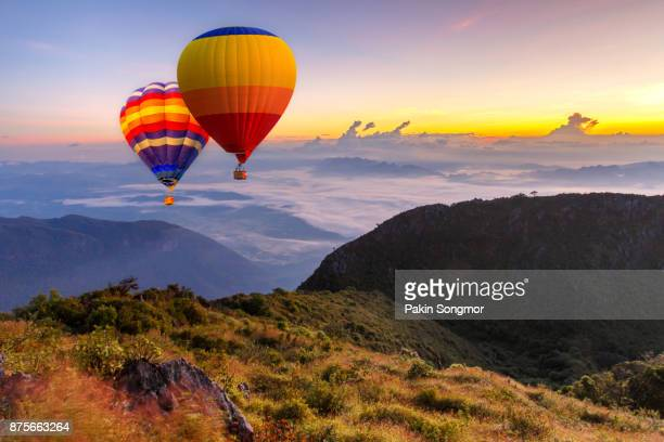 Colorful hot-air balloons flying over the Doi Luang Chiang Dao with sunrise and morning mist at Chiang mai, Thailand.